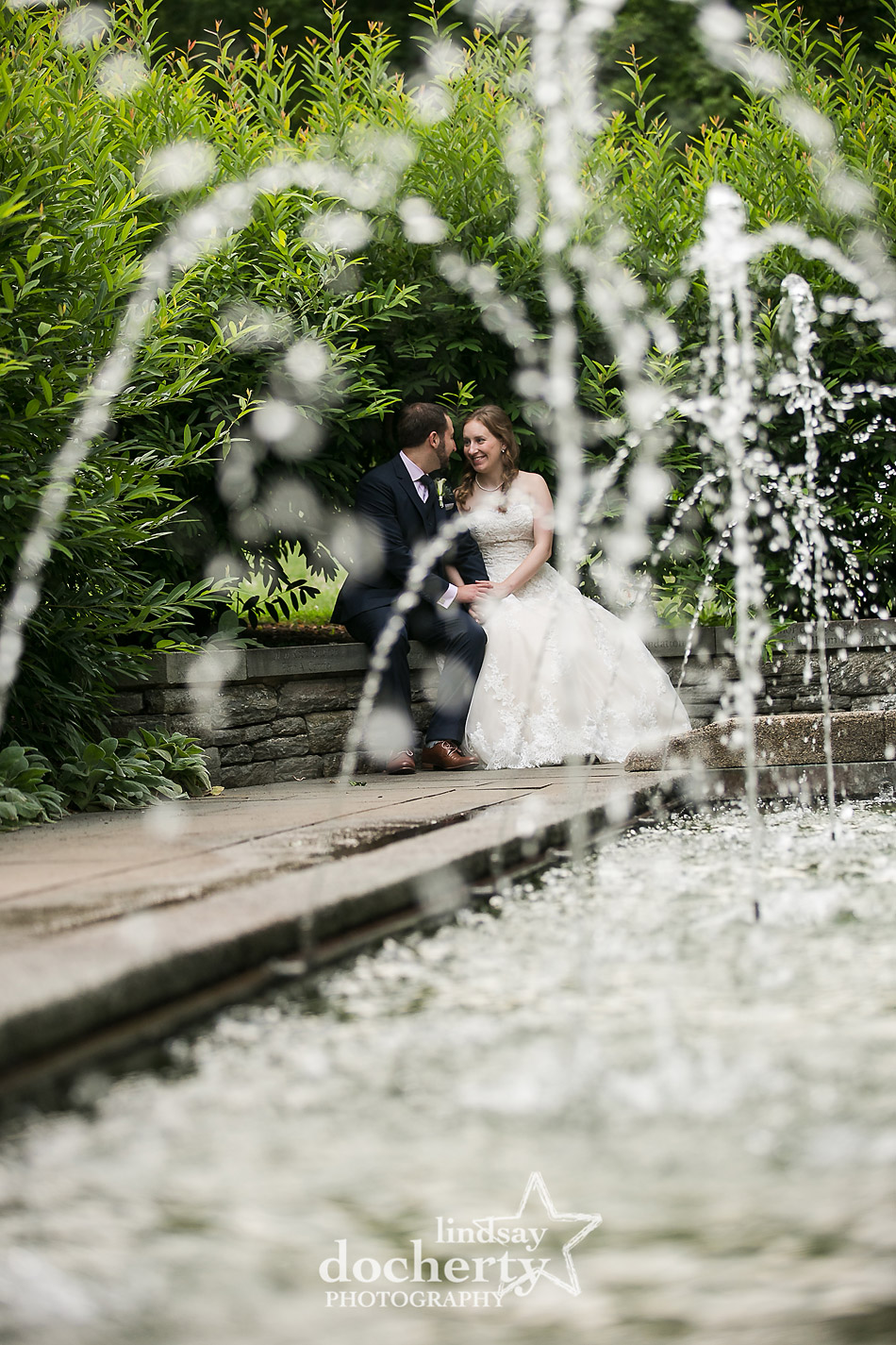 bride and groom sitting together by the fountains at Morris Arboretum