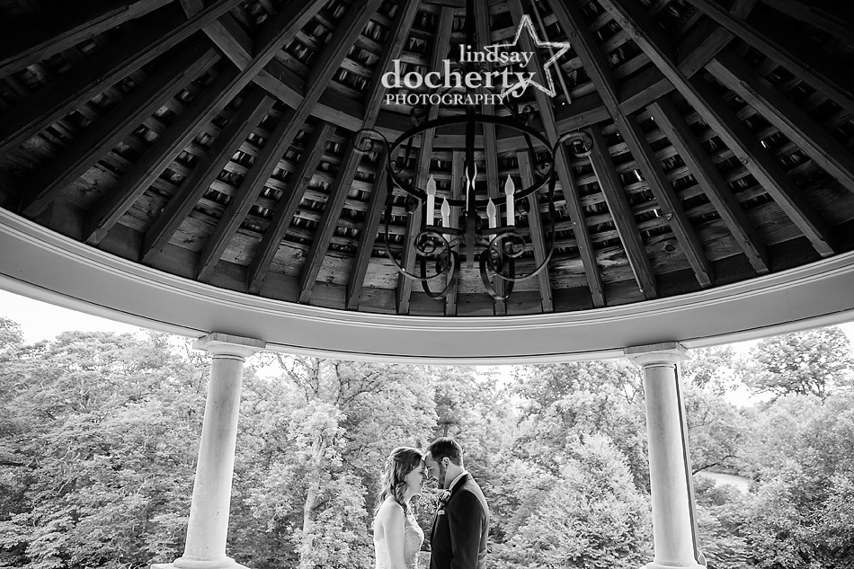 bride and groom under gazebo ay Morris Arboretum in Philadelphia