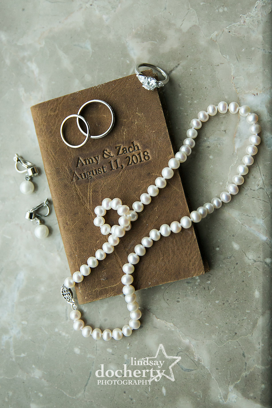 brides jewelry and couples vows in leather notebook