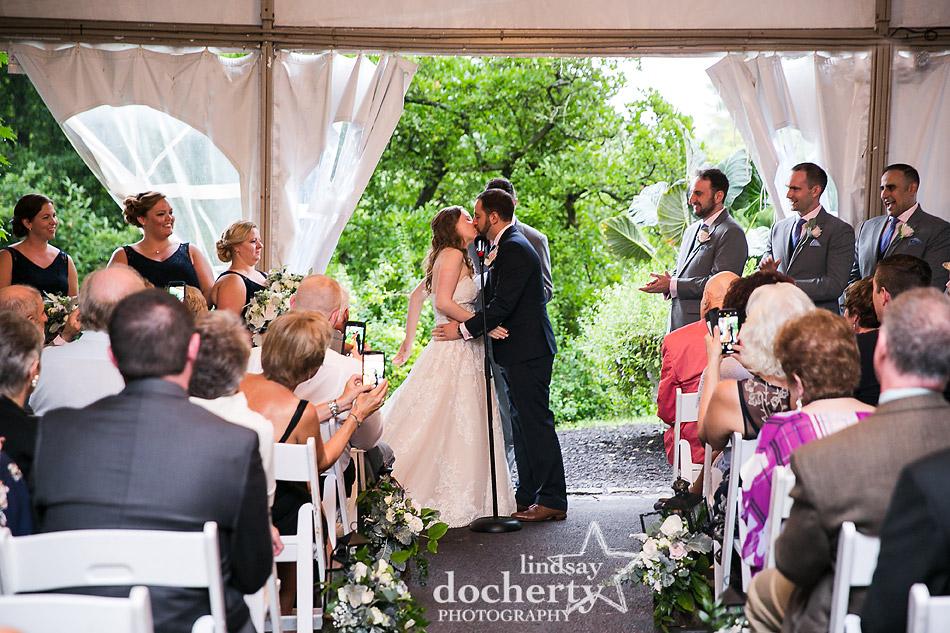 first kiss at wedding ceremony on rainy wedding day at Morris Arboretum
