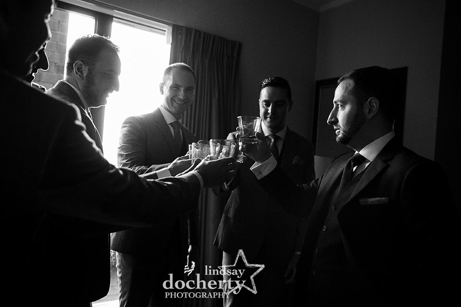 groom and groomsmen toasting with fancy bourbon before wedding ceremony