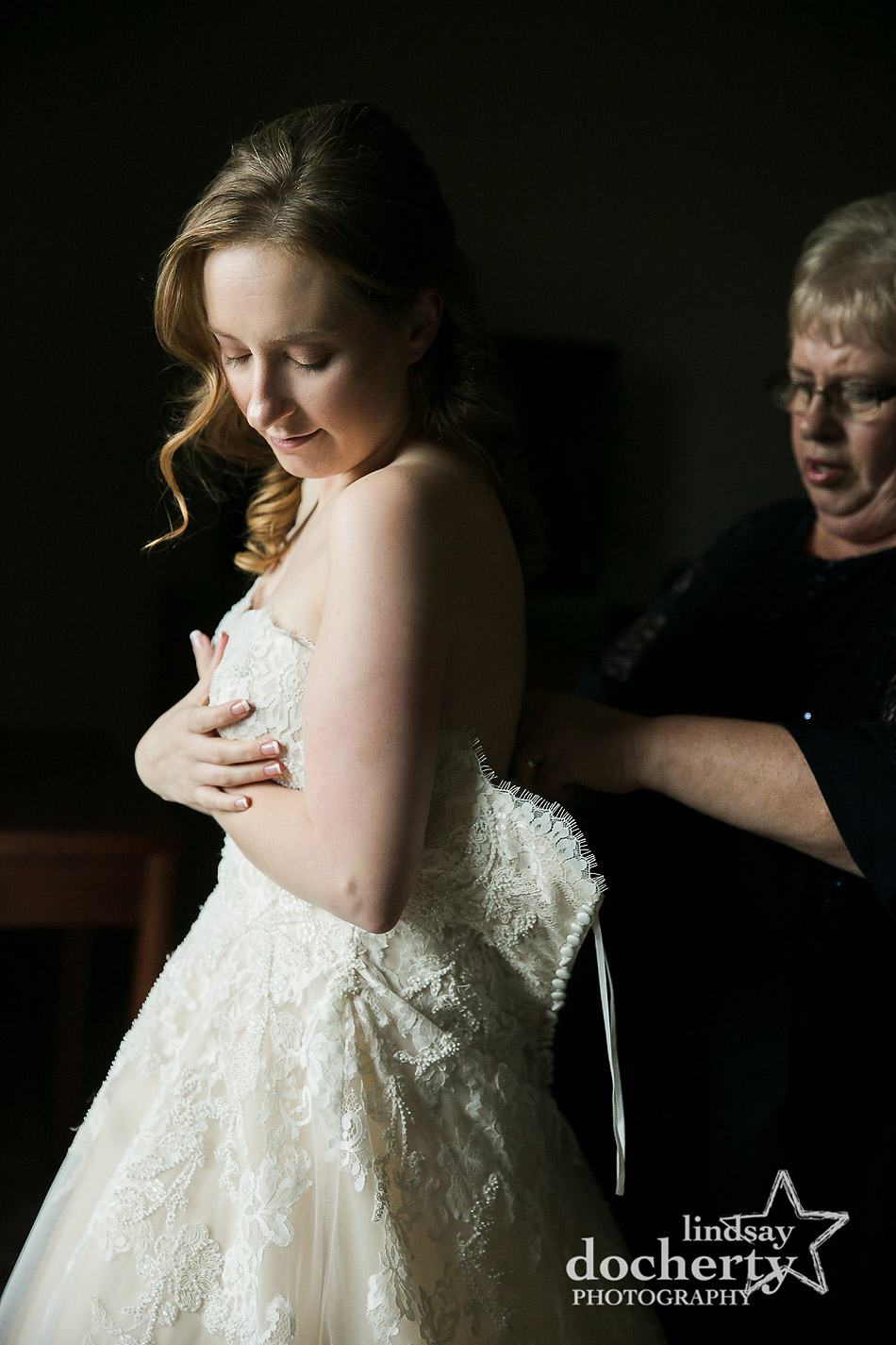mother of bride helping bride into dress on morning of wedding day