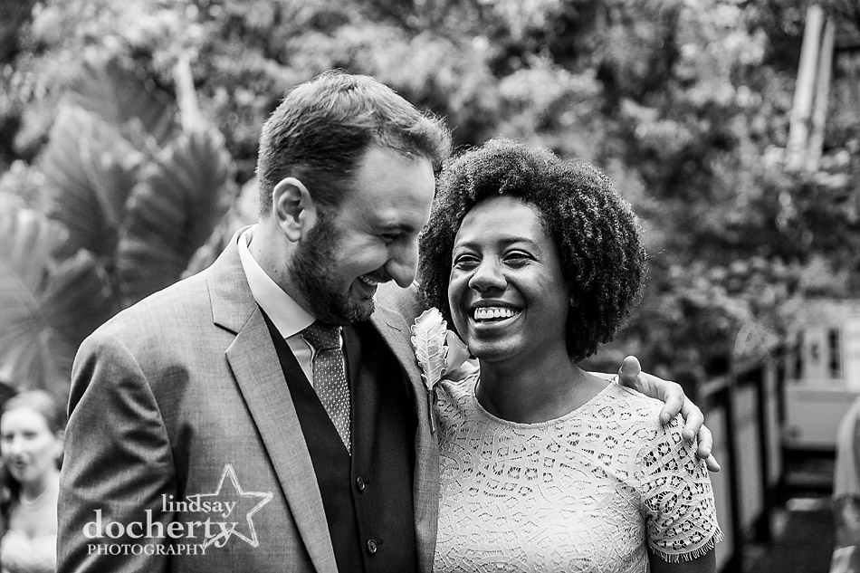 sweet couple laughing together during wedding reception at Morris Arboretum