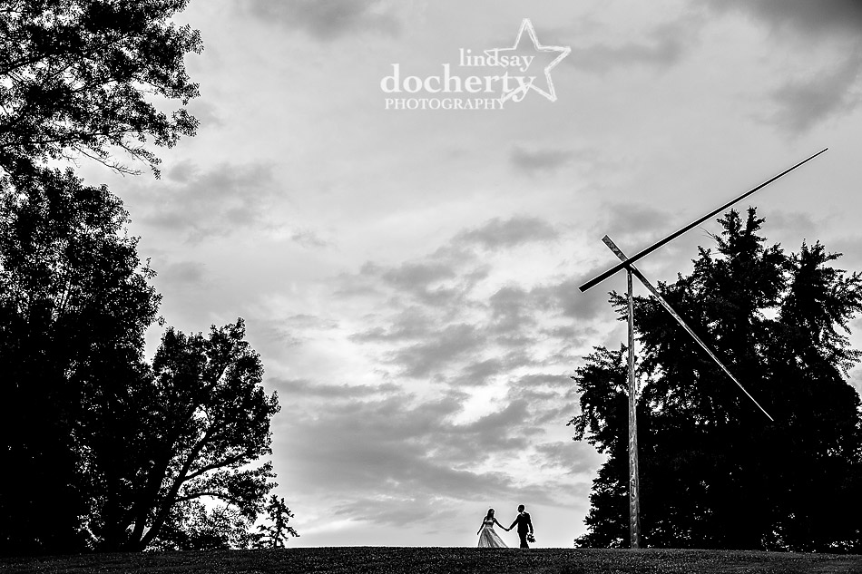 wedding couple walking in silhouette along ridge at Morris Arboretum