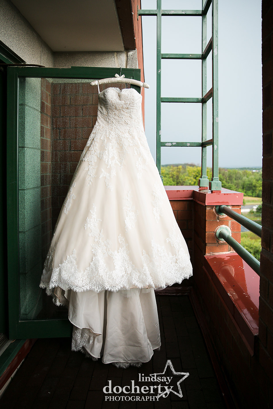 wedding dress hanging up ooutside on rainy wedding day