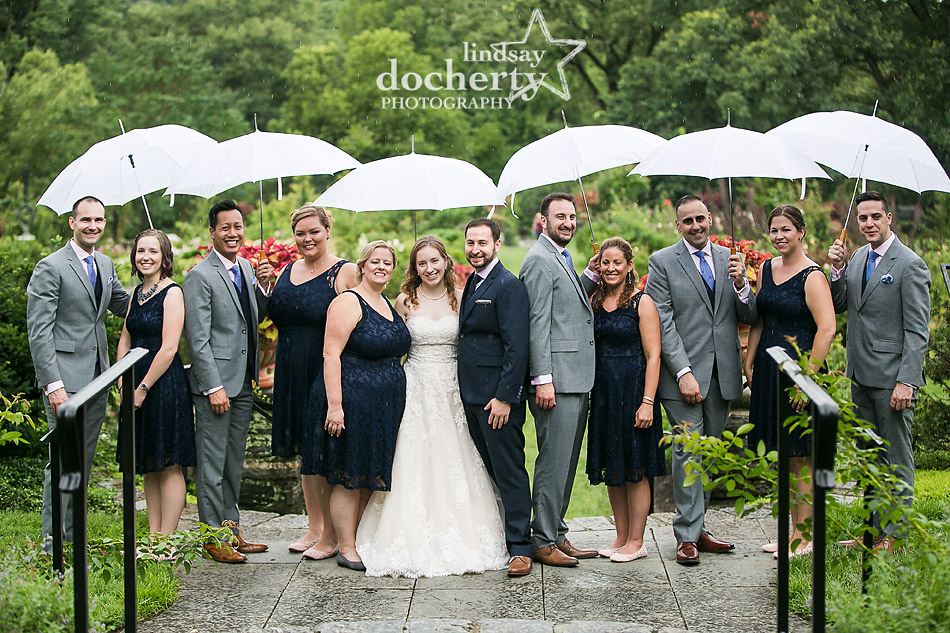 wedding party pictures in the rain with umbrellas at Morris Arboretum