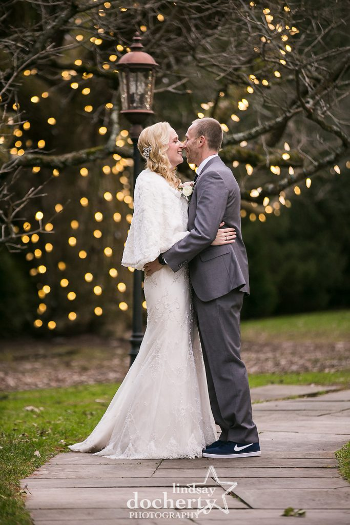 bride and groom kissing in front of lit tree outside of Aldie Mansion