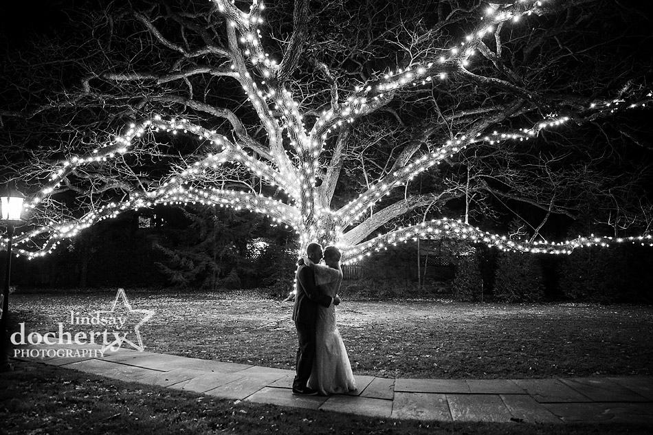 bride and groom outside by the big lit oak tree at Aldie Mansion