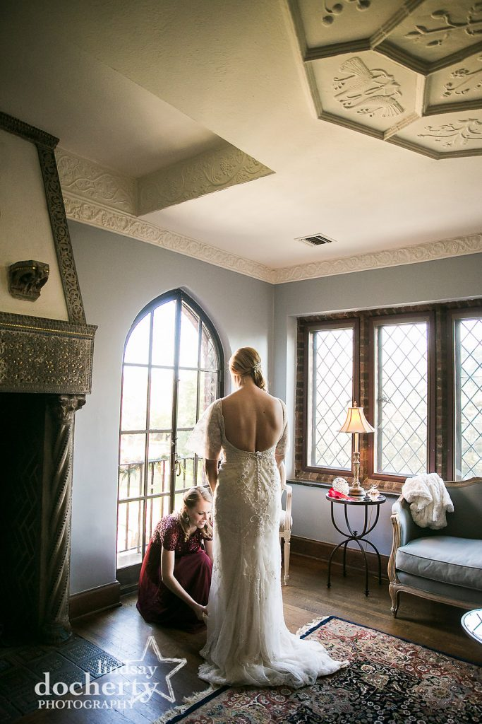 maid of honor helping bride get dressed on wedding day