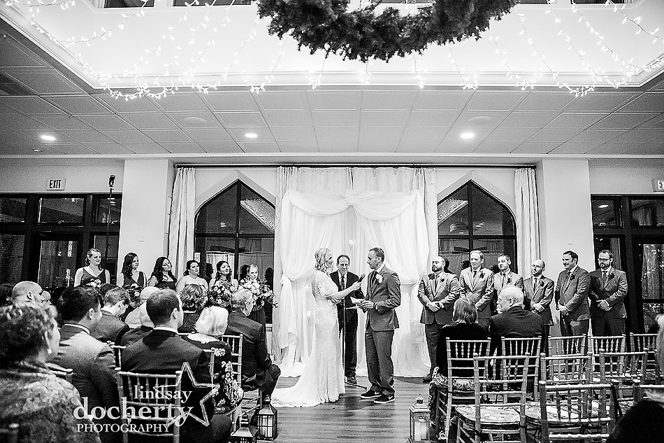 reciting vows between bride and groom on wedding day inside at Aldie Mansion