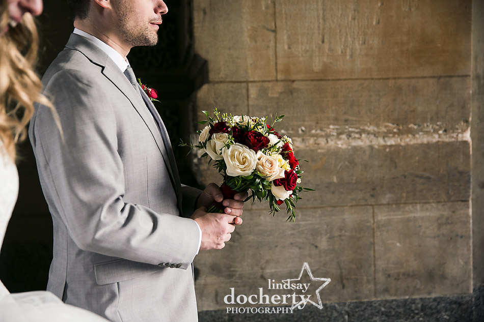 groom carrying red and white bouquet of roses for bride