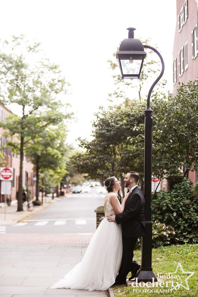 wedding day couple against lamppost in Washington Square Park in Philadelphia