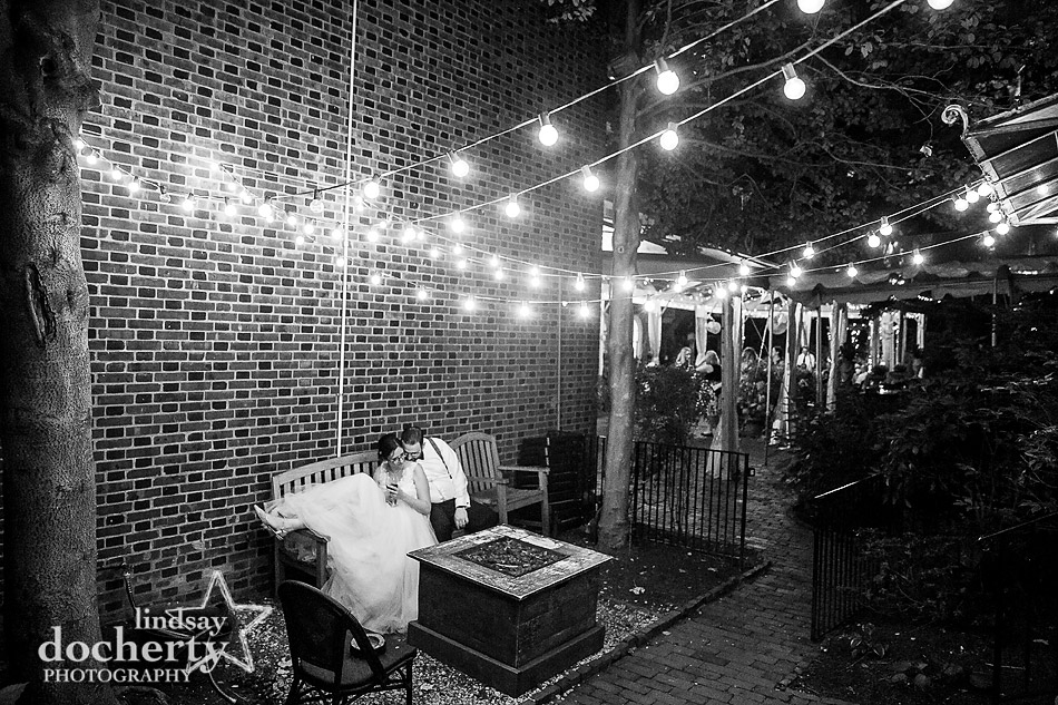 bride and groom cuddling late at night under bistro lights at Morris House Hotel in Philadelphia