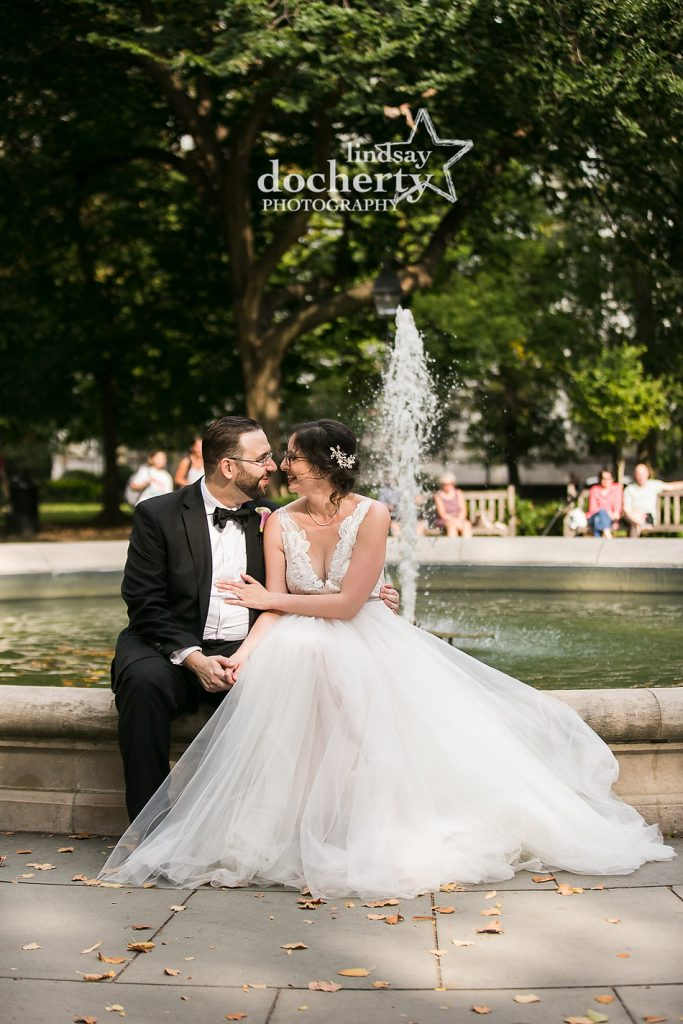 bride and groom in front of fountain in Washington Square Park in Philadelphia