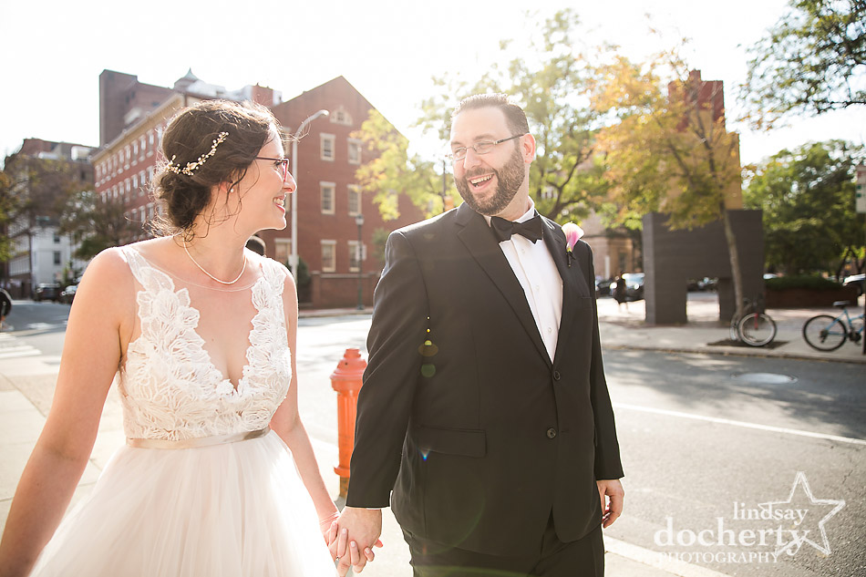 bride and groom walking down Philly street in sunlight