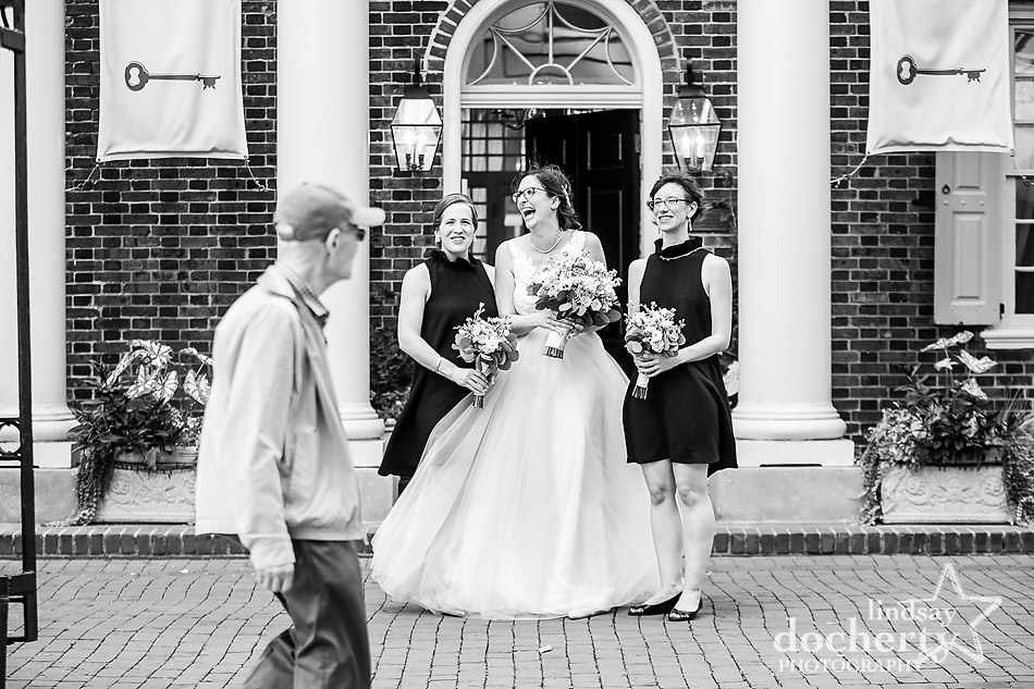 bride laughing with bridesmaids while onlooker walks past