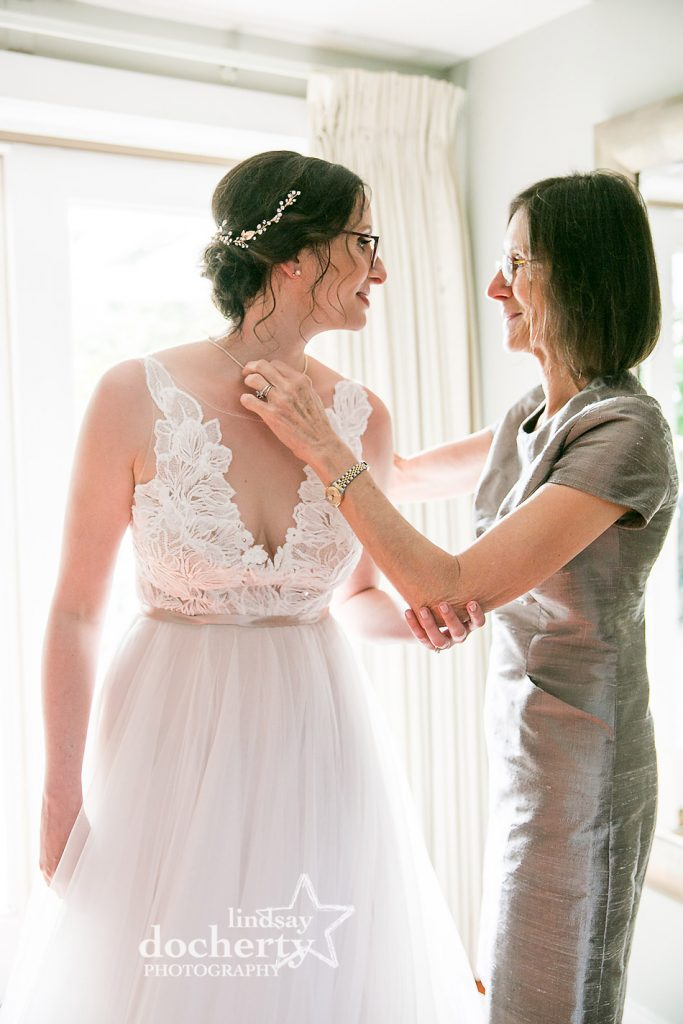 brides mom puts on heirloom pearl necklace