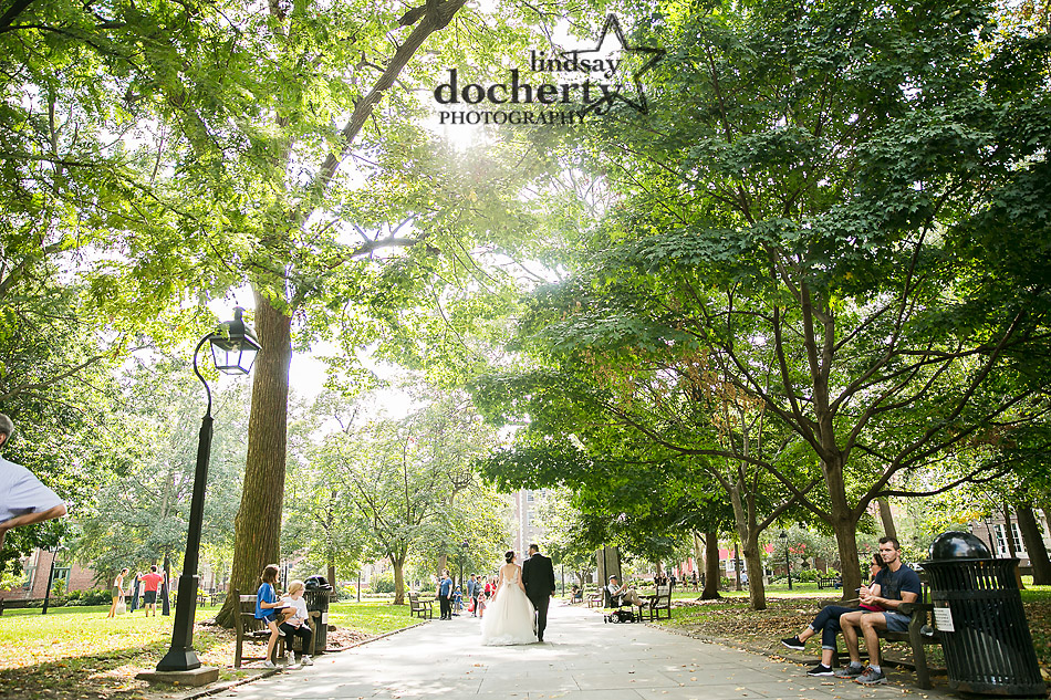 bride and groom walking down gorgeous tree lined path in Washington Square Park