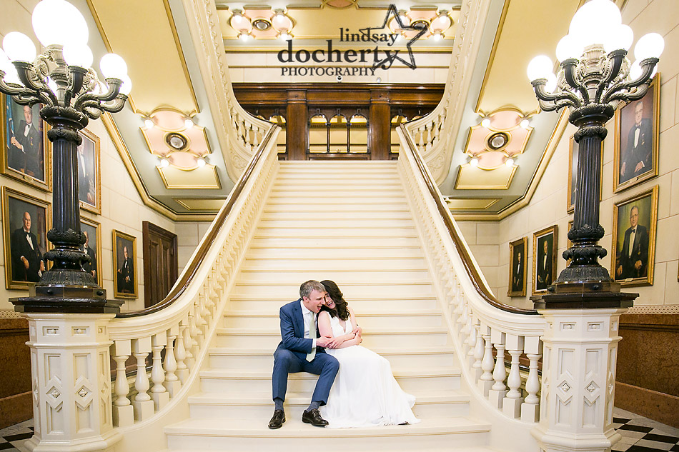 bride and groom cuddling together on grand staircase at ONE North Broad in Philadelphia