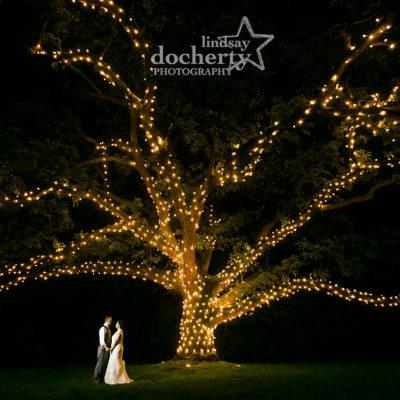 Nighttime wedding at Aldie Mansion under big oak tree with lights