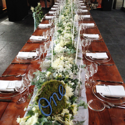 farmhouse table, skinny taper candles, floral table runner with eucalyptus and moss table number reception dinner at Castello di Vincigliata destination wedding in Italy