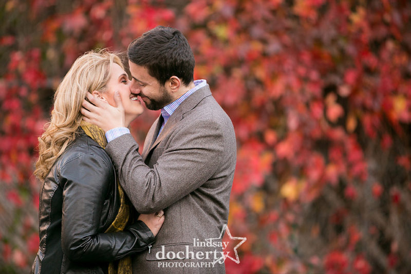 Romantic kiss at fall engagement session in Philadelphia against red leaves