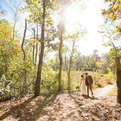 bride and groom walking through woods at Camp Ockanickon wedding in New Jersey