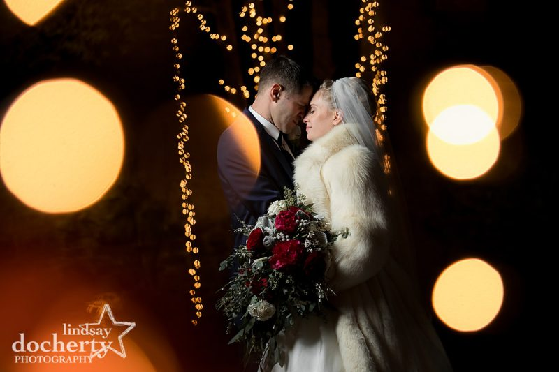 bride and groom in Christmas lights at winter wedding at Holly Hedge Estate
