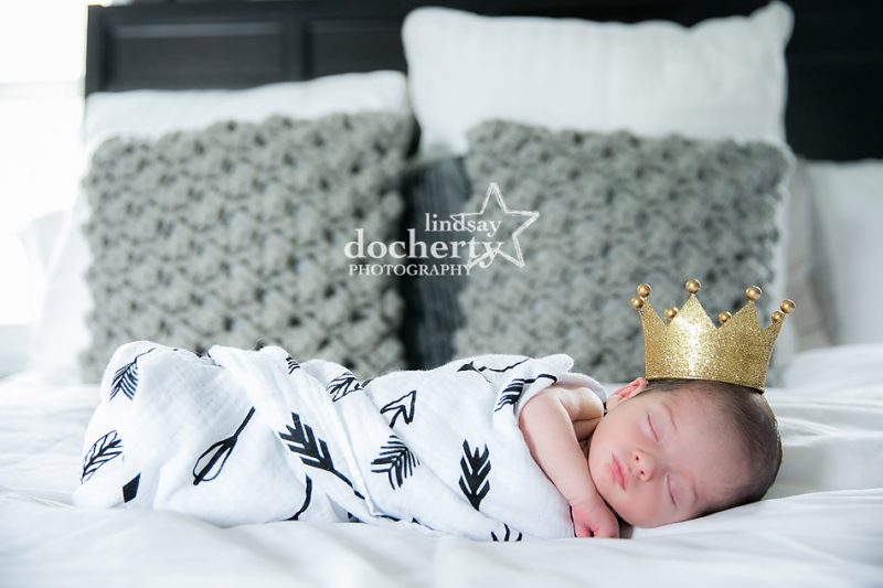 newborn baby boy bundled up with a gold crown like a king
