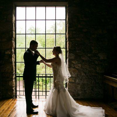 groom kissing brides hand at huge window at Holly Hedge Estate