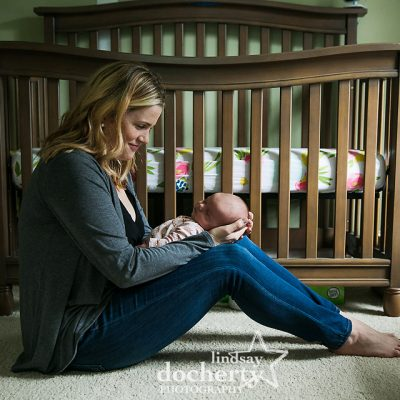 mother sitting on floor with newborn baby girl in front of crib