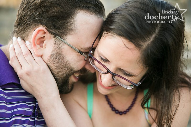 engaged couple in glasses giggling closeup