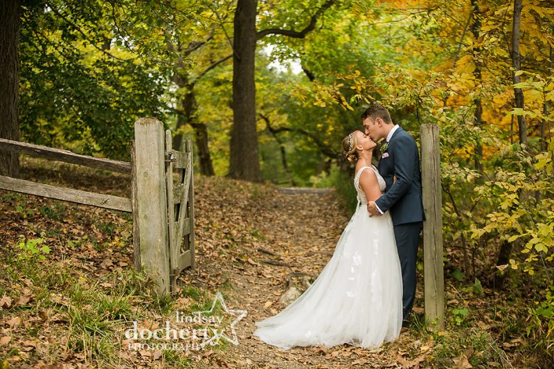 groom kissing brides nose on path at Bartram's Gardens fall wedding
