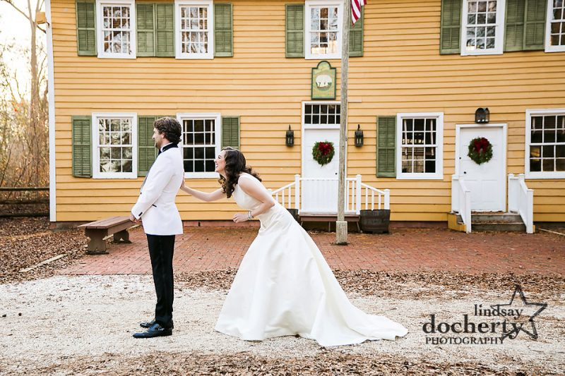 bride sneaking up on groom for first look on wedding day at Cold Spring Village